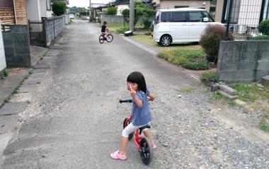 おさがりのランニングバイクに乗る女の子